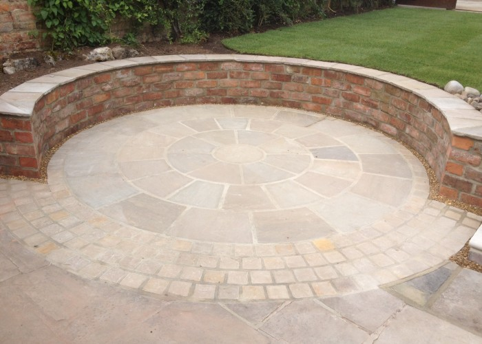 A natural stone circle with reclaimed brick wall