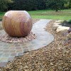 A large rainbow stone sphere water feature with natural stone setts and rockery thumbnail
