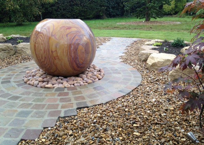 A large rainbow stone sphere water feature with natural stone setts and rockery